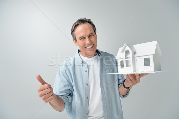 portrait of smiling mature man with house model showing thumb up Stock photo © LightFieldStudios