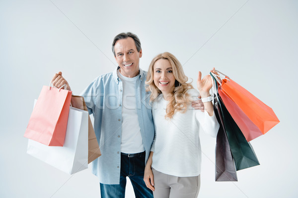 Happy middle aged couple holding shopping bags and smiling at camera   Stock photo © LightFieldStudios