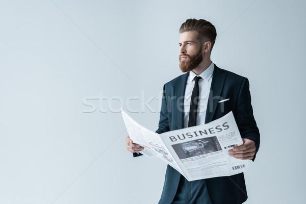 Handsome bearded businessman holding newspaper and looking away on grey Stock photo © LightFieldStudios