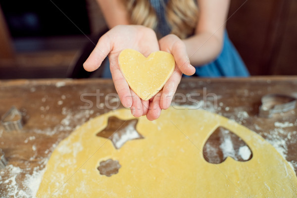 partial view of girl holding raw heart shaped dough for cookie  Stock photo © LightFieldStudios
