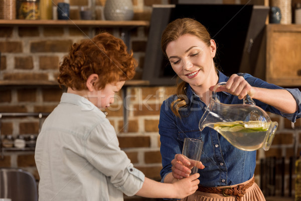 mother pouring lemonade in glass Stock photo © LightFieldStudios