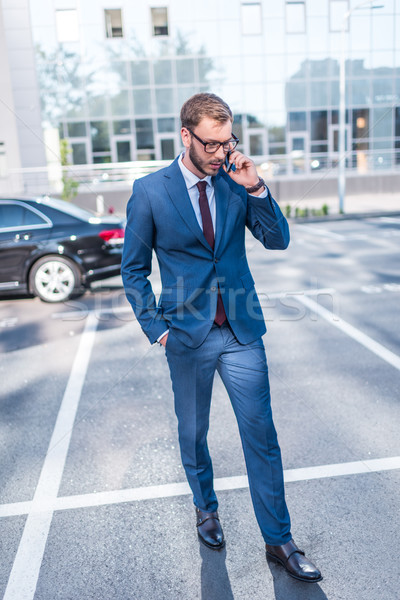 Stock photo: businessman with smartphone on parking