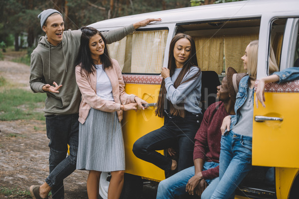 Stock photo: multiethnic friends in retro minivan
