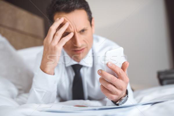 üzletember ágy okostelefon problémás hivatalos visel Stock fotó © LightFieldStudios