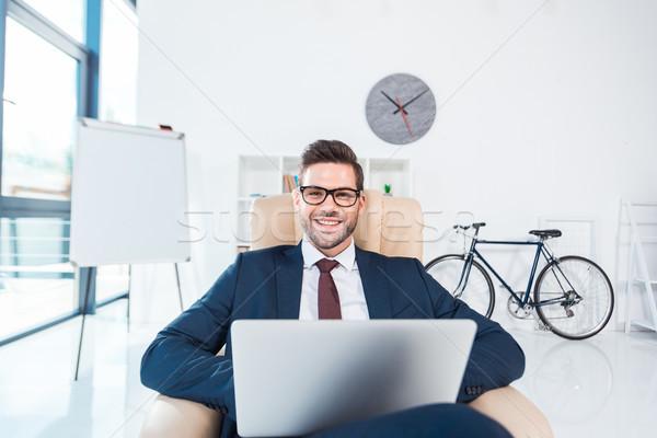 üzletember laptopot használ iroda jóképű fiatal szemüveg Stock fotó © LightFieldStudios