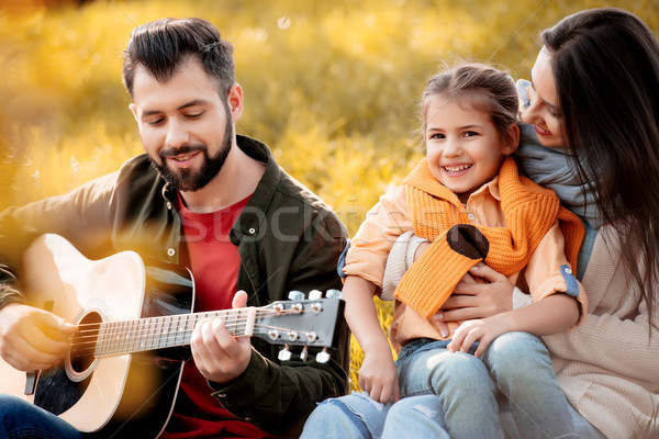 Stock photo: Family relaxing on grassy hill