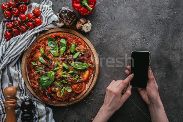 Shot kobieta smartphone konkretnych tabeli pizza Zdjęcia stock © LightFieldStudios