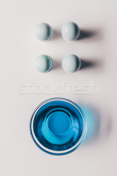 top view of four easter eggs on stands and glass of paint on white surface Stock photo © LightFieldStudios