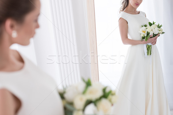 bride in traditional dress with wedding bouquet looking at her reflection in mirror Stock photo © LightFieldStudios