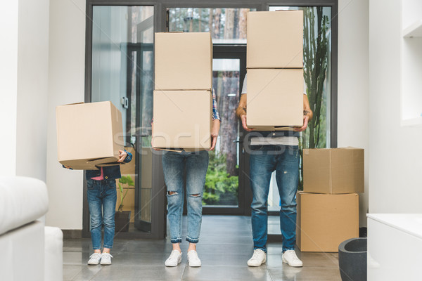 partial view of family holding cardboard boxes at new home, moving home concept Stock photo © LightFieldStudios