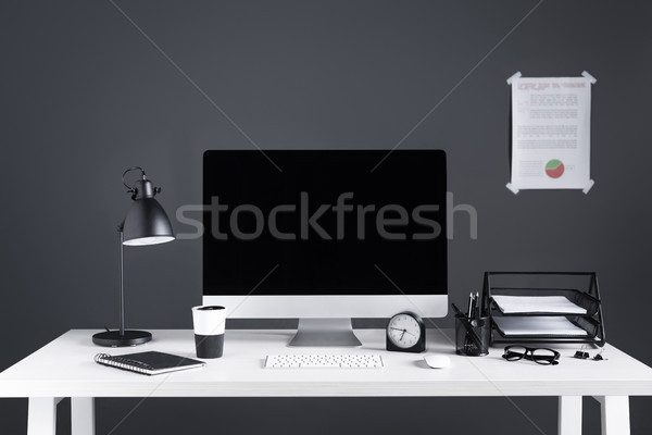 desktop computer with blank screen, business chart, clock and office supplies at workplace  Stock photo © LightFieldStudios