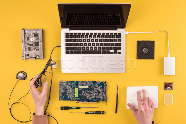 partial top view of person holding eyeglasses and fixing laptop on yellow Stock photo © LightFieldStudios