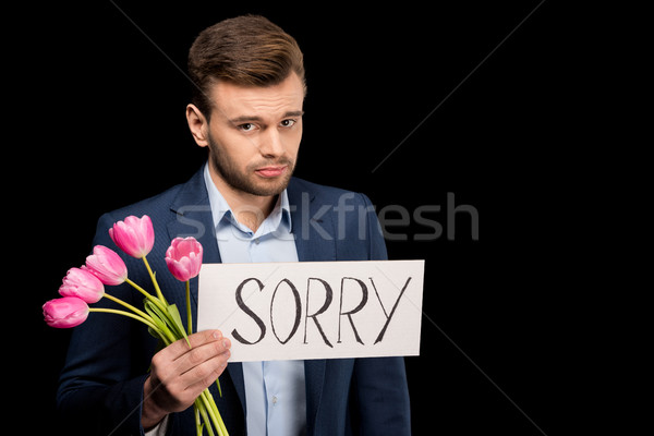 Ashamed young man with tulips and sorry sign looking at camera Stock photo © LightFieldStudios