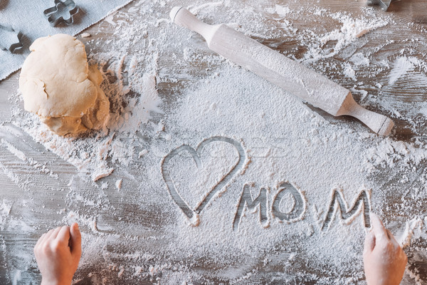 'Partial top view of child drawing heart symbol and word mom in flour on table, Mothers day concept Stock photo © LightFieldStudios