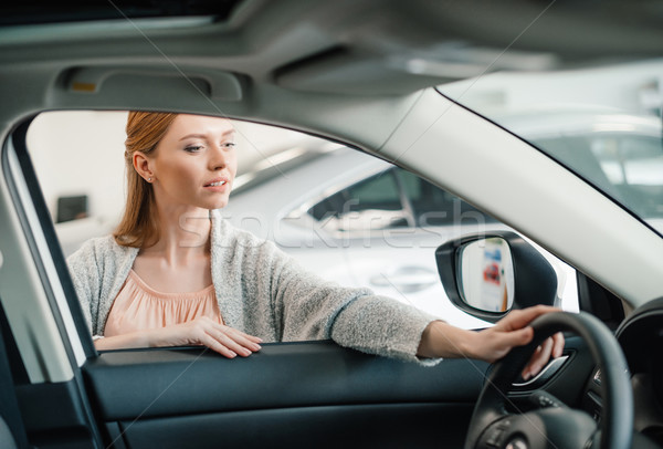 pensive caucasian woman choosing car in dealership salon    Stock photo © LightFieldStudios