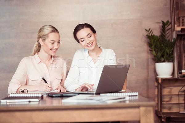 Deux séduisant souriant affaires utilisant un ordinateur portable prendre des notes Photo stock © LightFieldStudios