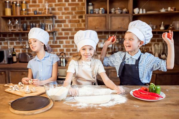 children making pizza dough and preparing pizza ingredients in kitchen Stock photo © LightFieldStudios