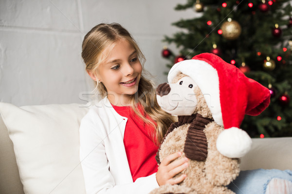 child with teddy bear at christmastime Stock photo © LightFieldStudios