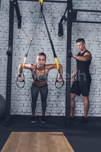 woman exercising with trx gym equipment Stock photo © LightFieldStudios