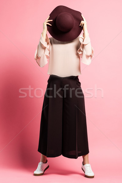 Woman covering face with hat Stock photo © LightFieldStudios