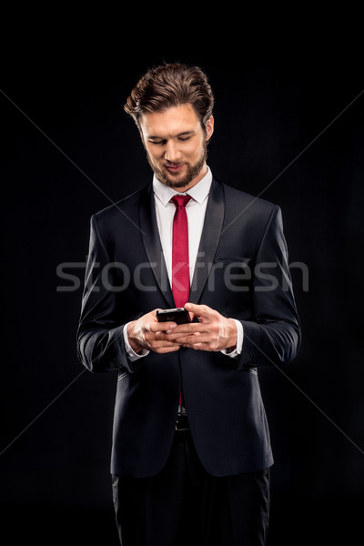Handsome businessman using smartphone Stock photo © LightFieldStudios