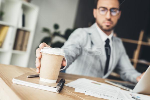 businessman taking disposable cup of coffee Stock photo © LightFieldStudios