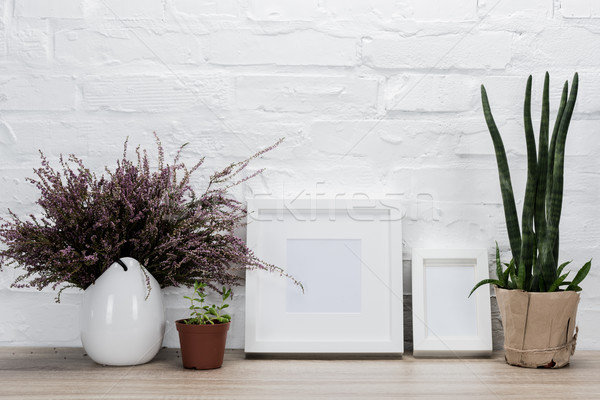 empty photo frames and flowers on tabletop Stock photo © LightFieldStudios
