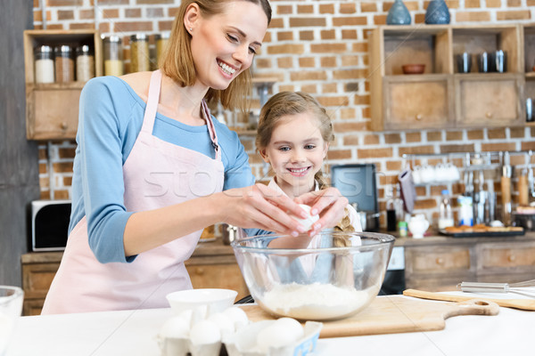 Stock photo: Happy mother and daughter preparing dough for home baking in kitchen