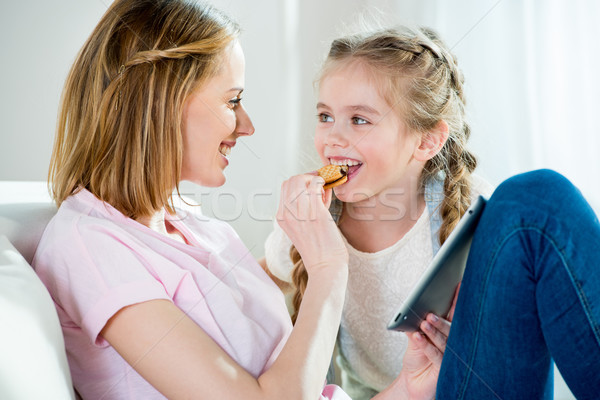Happy mother feeding daughter with cookie while using digital tablet Stock photo © LightFieldStudios