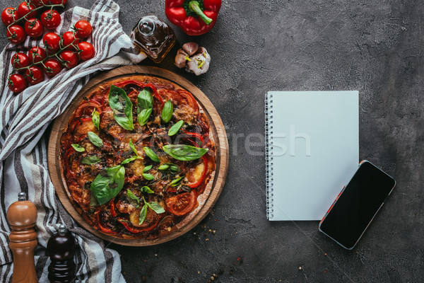 top view of freshly baked pizza with notebook and smartphone on concrete table Stock photo © LightFieldStudios