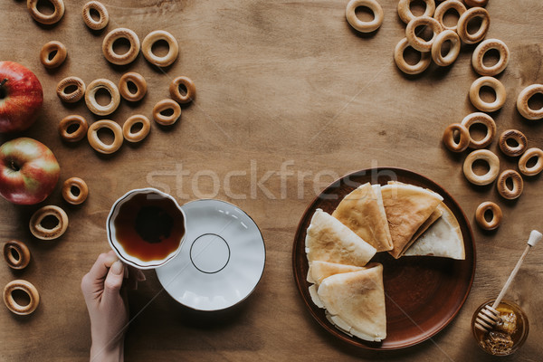 cropped shot of person drinking tea and eating pancakes at wooden table Stock photo © LightFieldStudios