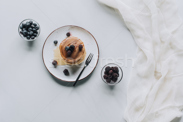 top view of tasty homemade pancakes with honey and fresh berries on grey  Stock photo © LightFieldStudios