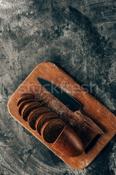 top view of arranged pieces of bread on cutting board with knife on dark surface with flour Stock photo © LightFieldStudios