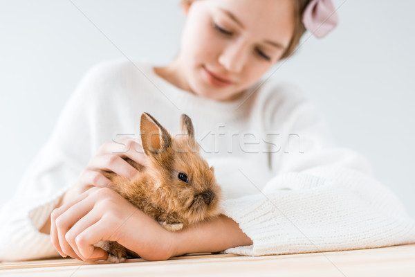 close-up view of smiling girl holding adorable furry rabbit on white  Stock photo © LightFieldStudios