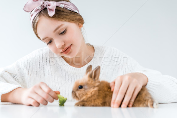beautiful smiling girl feeding rabbit with broccoli on white Stock photo © LightFieldStudios