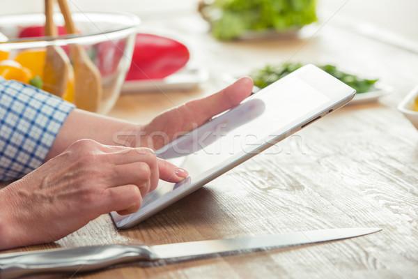 Woman using digital tablet in kitchen Stock photo © LightFieldStudios