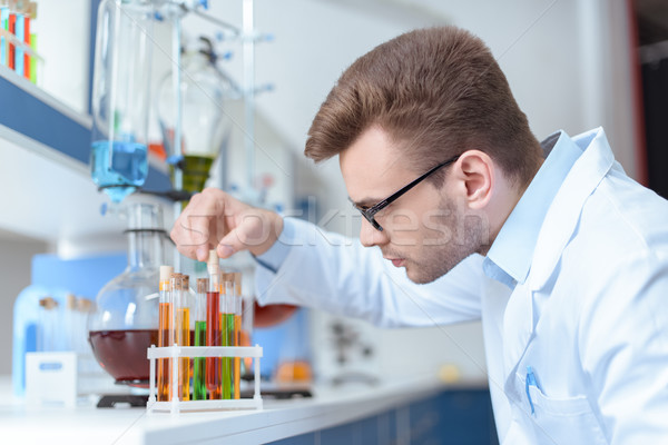 Side view of young man scientist holding test tube with reagent in lab Stock photo © LightFieldStudios
