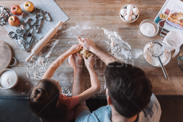 'Overhead view of father and daughter kneading dough at kitchen table Stock photo © LightFieldStudios