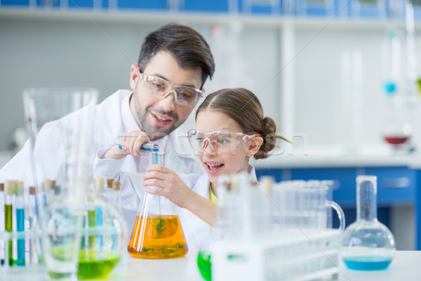 Man teacher and girl student scientists in protective glasses making experiment in lab Stock photo © LightFieldStudios