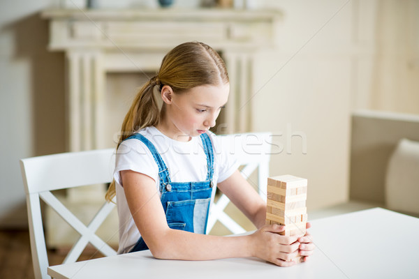 Concentrated preteen girl building tower from wooden bricks on table Stock photo © LightFieldStudios