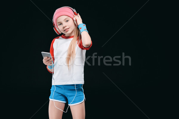Cute sporty girl in headphones using smartphone and smiling at camera, activities for children conce Stock photo © LightFieldStudios