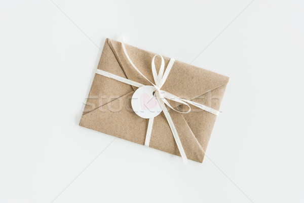 kraft envelope with teg with heart and ribbon isolated on white, wedding invitation card design conc Stock photo © LightFieldStudios