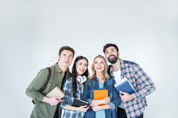 Stock photo: four young students in casual clothes holding books on white