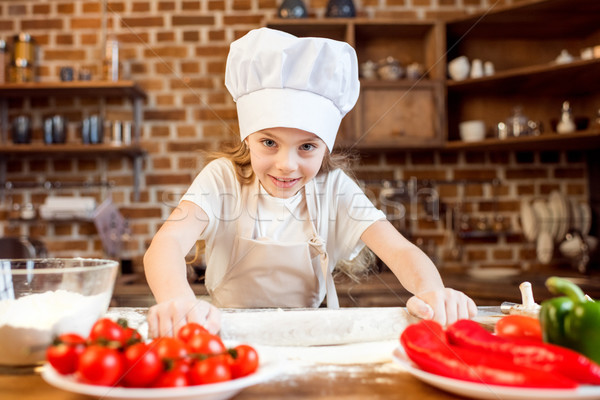 little girl making pizza dough with pizza ingredients on foreground Stock photo © LightFieldStudios