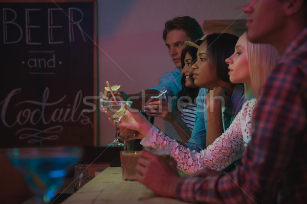 multiethnic friends drinking cocktails in bar Stock photo © LightFieldStudios