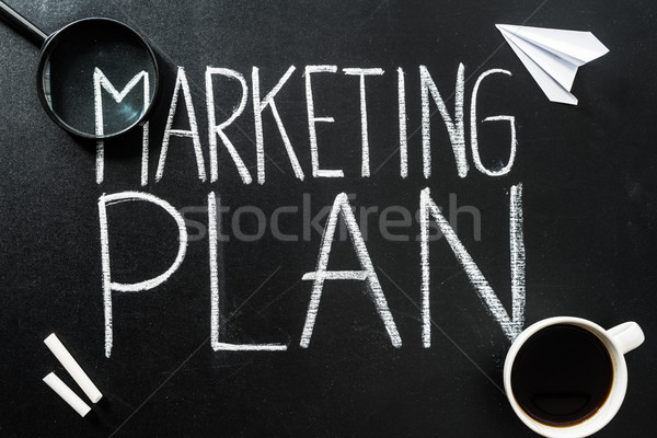 Top view of marketing plan lettering on chalkboard with cup of coffee and magnifier Stock photo © LightFieldStudios