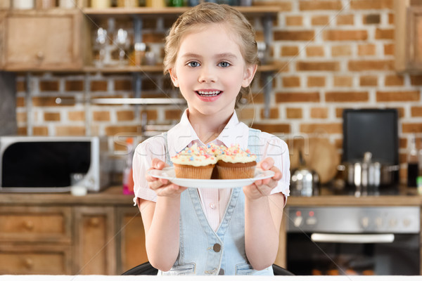 Happy little girl holding delicious cakes on plate and smiling at camera Stock photo © LightFieldStudios