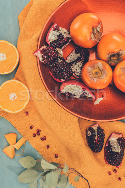 top view of yummy fruits on plate on orange tablecloth Stock photo © LightFieldStudios