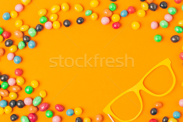 top view of party mask and sweets isolated on orange, purim holiday concept Stock photo © LightFieldStudios