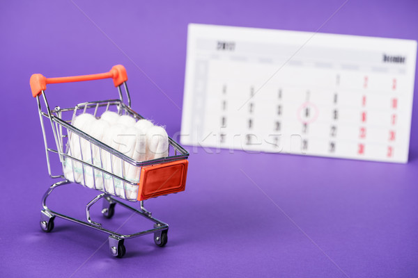 tampons in small shopping cart and calendar on purple Stock photo © LightFieldStudios